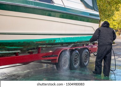 Man pressure washing boat hull with power washer