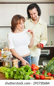 A man and pretty woman with vegetables in the kitchen of his home