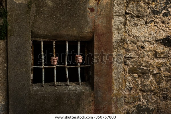 Man in prison and behind grate