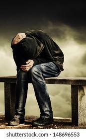 Man with problems. Man in hood with hands on his head sitting on the concrete bench. Drug addict concept.