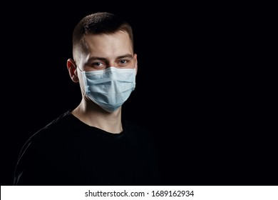 man with a procedure medical white or blue face mask from a coronavirus pandemic disease infection COVID-19 on black background