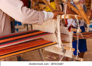 A man produces the fabric on a traditional loom in the Bedouin village, Egypt