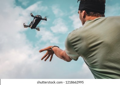 A man, a professional aerial photographer, launches a quadcopter or drone in the sky to take a video or photo of a terrain from a height. Man operating a drone with remote control.