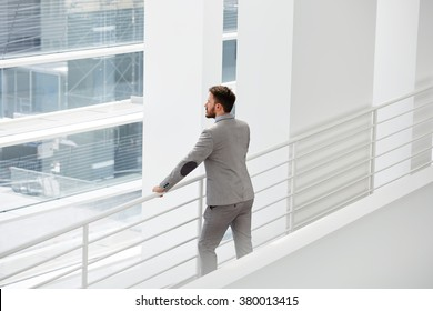 Man professional architect looks at building object which he by using logistical resources create a project organization space, male skilled manager watching at big office window during his work break