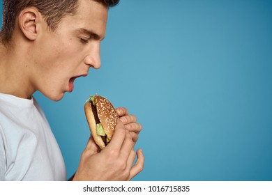 man in profile eating a hamburger on a blue background