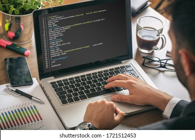 Man programmer making a code on a computer screen, office, business background. Software, programming concept