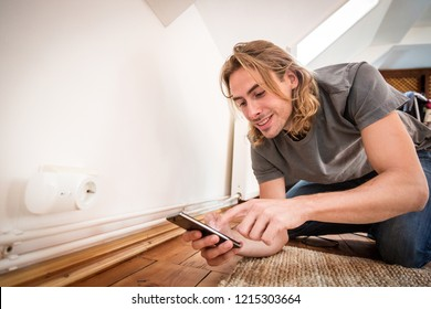 Man Programming A Power Outlet Using His Phone