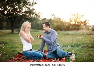 A man proposes to a girl in a park at a picnic