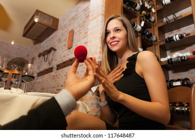 Man proposing marriage to a surprised woman