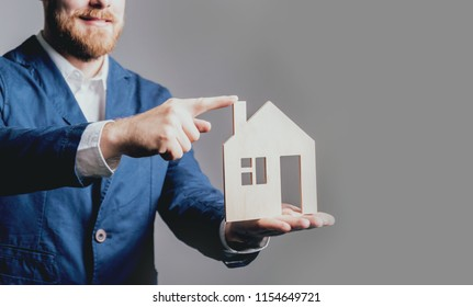 Man proposing signing a estate insurance policy, the agent is holding the wooden house model. Estate insurance concept. Advertisement of real estate agency