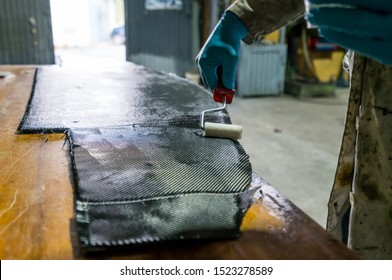 Man with protections on hands, eyes and mask, repairing a piece of carbon and epoxy resin.