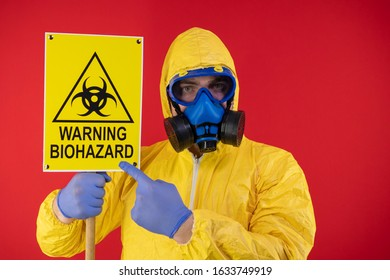 A man in a protective chemical mask and a protective yellow suit with a banner in his hand with the words biohazard. Biohazard concept
