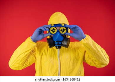 A man in a protective chemical mask and a protective yellow suit holds his hands by the mask. Biohazard concept