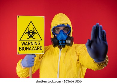 A man in a protective chemical mask and a protective yellow suit with a banner in his hand with the words biohazard shows a stop sign. Biohazard concept