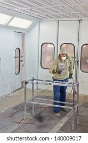 Man in protective clothes and respirator works in paint-spraying booth, painting car details with airbrush