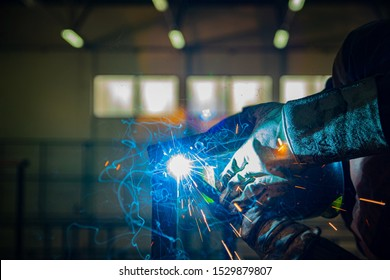 A man in protective clothing welding metal parts