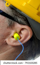 man with protective ear plugs and helmet