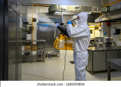 man in protective equipment disinfects with a spray gun industrial surfaces due to coronavirus covid-19 .Virus pandemic