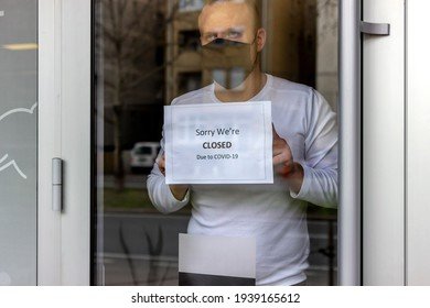 Man with protective face mask closing business activity due to covid-19 emergency lockdown quarantine. Man with protective face mask at fitness center entrance holding closing sign due to coronavirus.