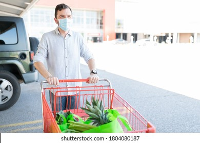 Man in protective face mask pushing shopping cart while walking against supermarket