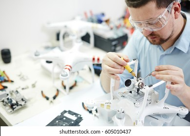 Man in protective glasses attaching action camera to quadcopter drone on table  with different tools in modern workshop