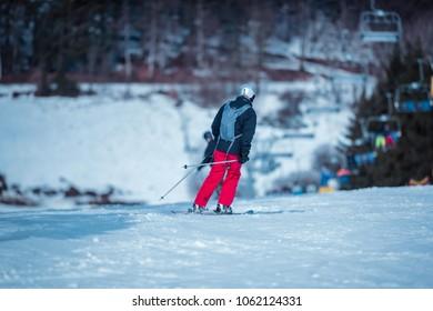 Man in protective helmet skiing on ski slope. Winterberg. Germany. Rear view.