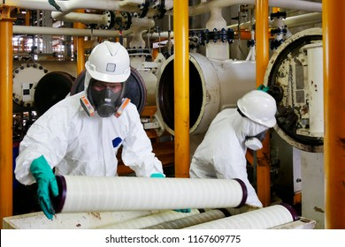 Man with protective mask and protective clothes in danger area. Worker change the filter at oil and gas plant.