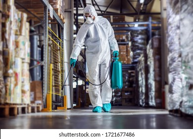 Man in protective suit and mask disinfecting warehouse full of food products from corona virus / covid-19.