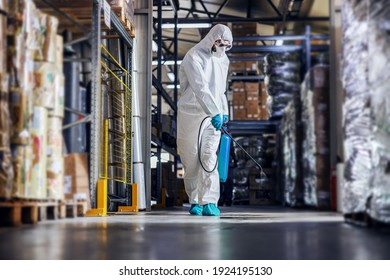 Man in protective suit and mask disinfecting warehouse full of food products from corona virus, covid-19.