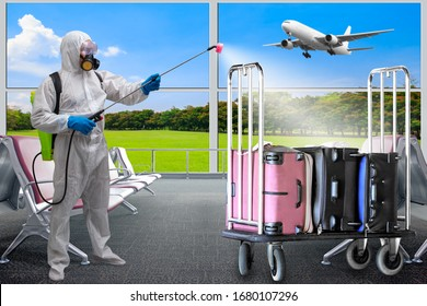 Man in protective suit spraying luggage bag cart and interior of at terminal in airport using chemical agents to stop spreading virus infections.