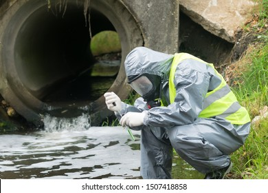 a man in a protective suit takes a sample of water from the river after the release of chemical waste