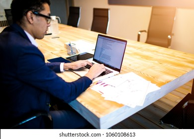 Man proud CEO keyboarding on laptop computer while sitting in office at table with paper documents and working tools. Male entrepreneur typing text on notebook. Workplace with netbook