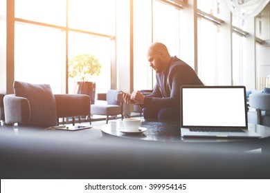 Man proud CEO is ordering on-line via cell telephone car for business trip, while is sitting in co-working cafe near table with open laptop computer with empty copy space screen for your advertising