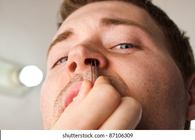 Man pucking nose hair with tweezers while facing camera