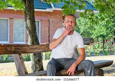 Man puffing on a cigarette outdoors in the garden as he sits on a wooden bench in the shade of a tree enjoying the summer day
