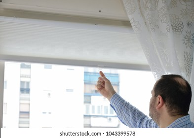 Man pulling down a white blind on a window