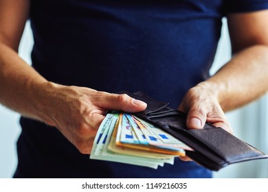 The man pulling euro banknotes out of brown wallet