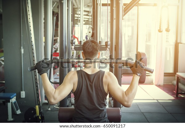 Man pulling up on horizontal bar in a gym. Athlete muscular fitness.