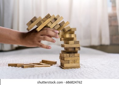 Man pulling out wood block fail on building tower at home and drape background