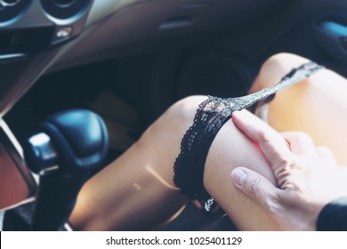 Man pulling panty liner of woman while driving or sitting in a car - sex in car dangerous drive behave concept