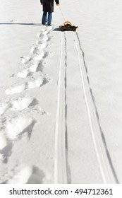 a man pulling a sledge in the deep snow, footprints and tracks