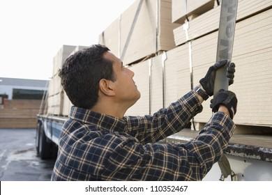 Man pulling trailer belt after loading wooden planks
