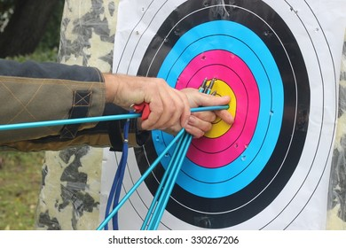 The man pulls the arrow from the target