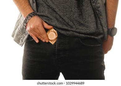 man pulls a condom out of his pants in studio