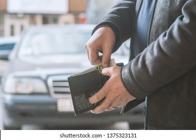 man pulls money out of his wallet