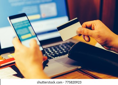 The man pulls out credit card from his wallet to pay for the purchase via a smartphone on the background of laptop. Man considers expenditures on a cash receipt. Mobile banking concept. Toned photo.