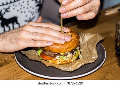 A man pulls out a fixer from a juicy, fresh burger and prepares to eat it