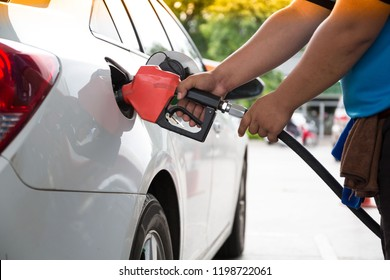man pumping gasoline fuel in car at gas station-transportation and ownership concept