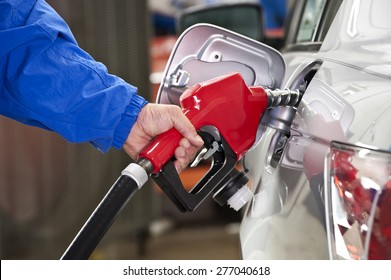 Man Pumping Gasoline Into Silver Car With Red Gasoline Nozzle