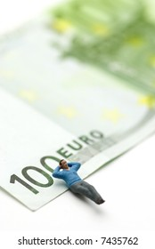 a man (puppet) sleeping on a Euro paper currency